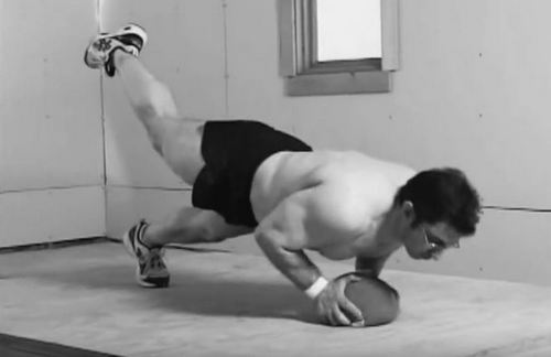 Brooks Kubik performing a pushup with one leg elevated from the ground and with both hands on a medium-sized ball.