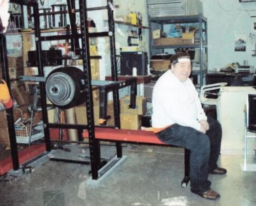 Chris Paul Bostick sitting at the edge of a weight bench attached to a self-made leverage machine.