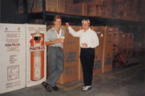 Clarence Harrison standing next to son Todd in front of big boxes in a plumbing-supply warehouse