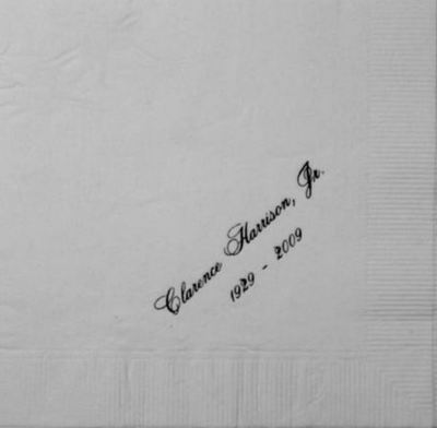 "White napkin with engraged in black cursive letters across it, ""Clarence Harrison, Jr. 1929 - 2009"""