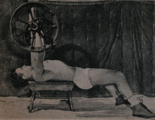 Clarence Harrison bench pressing a wagon-wheel barbell on an old wooden stool