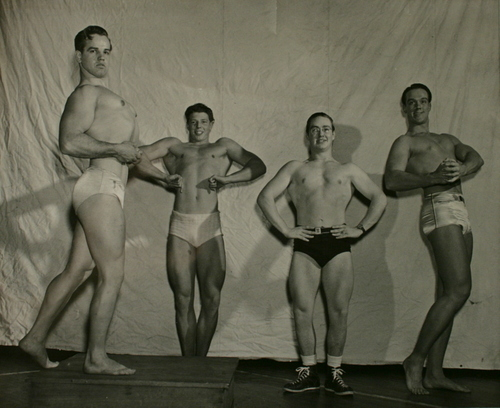 Clarence Harrison doing a side chest pose during a posedown with David Robinson, Richard Flanigan, and Ralph Cameron during the 1949 Mr. Louisville competition