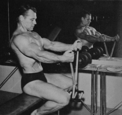 John Grimek working his chest with a crusher apparatus.
