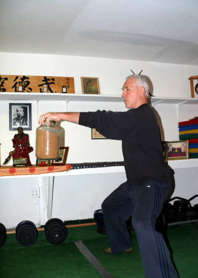 Peter yates demonstrating the Tip Hold exercise, using a jar, for grip building