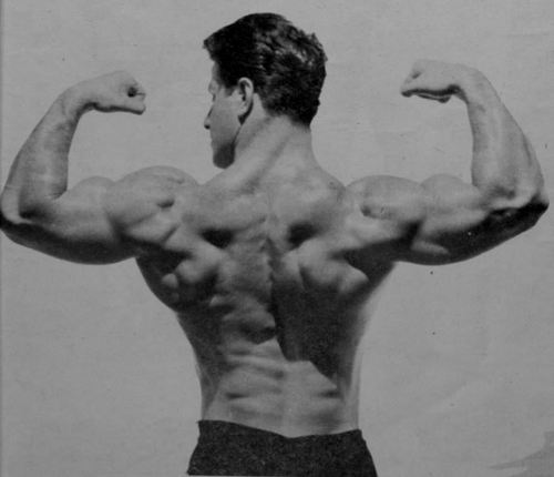 Reg Park doing a double-biceps pose and showing his muscle-packed back