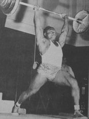 Clair Warner lifting a heavy barbell overhead.